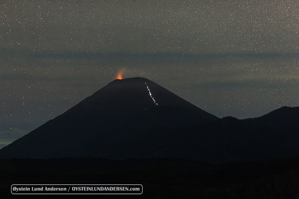 Semeru erupts at night, hikers seen climbing.