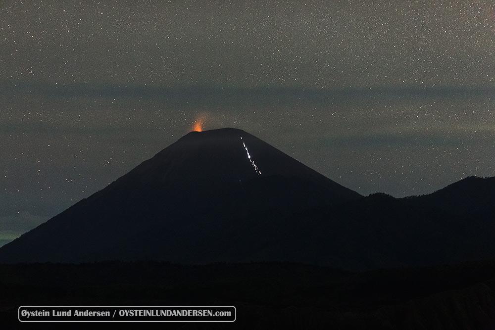 Semeru erupts at night, hikers seen climbing.