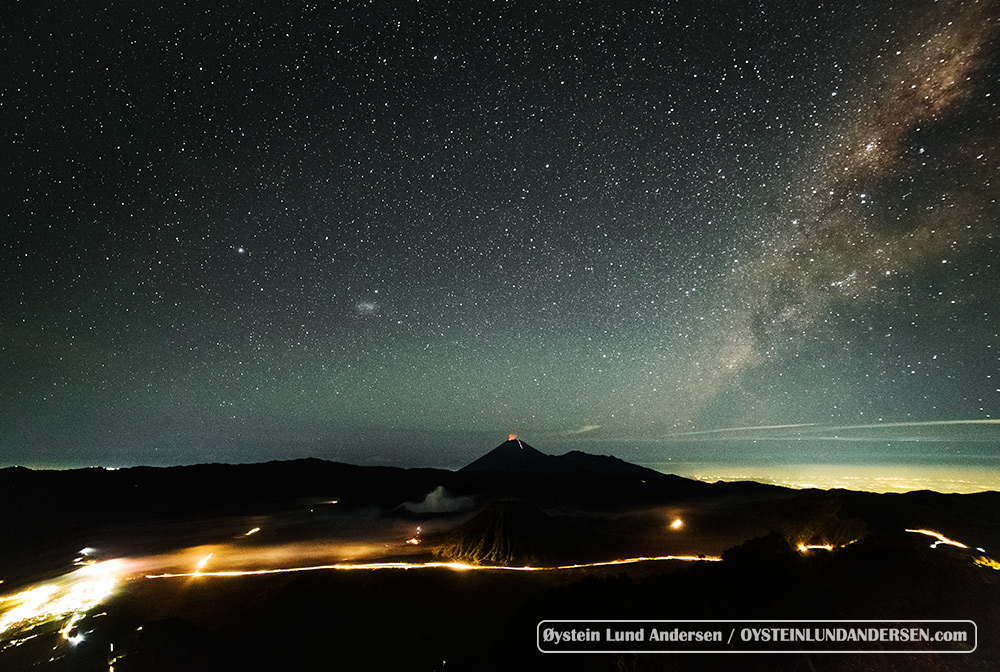 Looking over the Tengger caldera, bromo and Semeru at night, and the center of the milky way is visible in the west. Semeru can be seen erupting in the background.