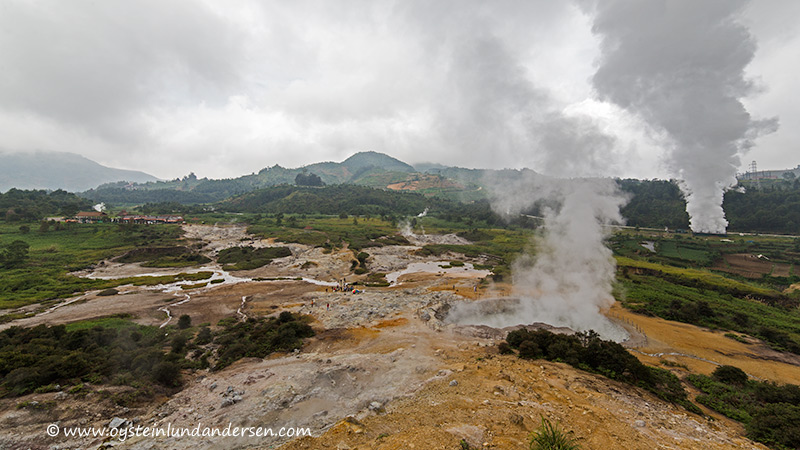 7.The Sikidang crater and the hydrothermal plant steaming in the background.