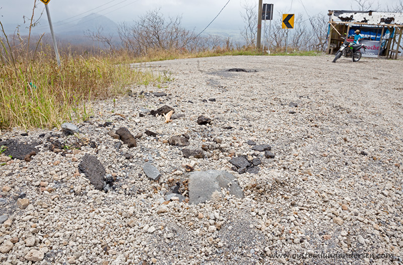 24. The volcanic-blocks are heavy, on this photo it has penetrated the asphalt of the road. (2km from the crater area) (22th February - 12:11)