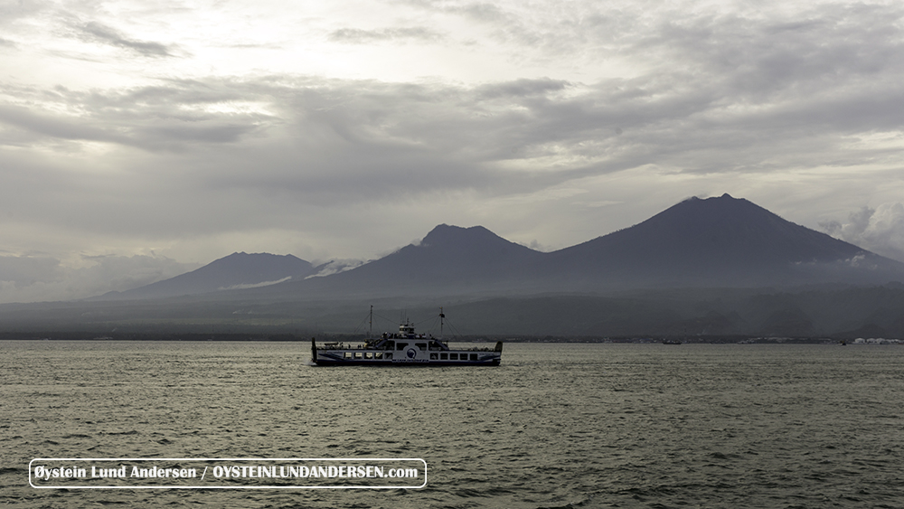 Boat on the strait between Java and Bali. Ijen volcano complex in the foreground and Raung volcano in the background